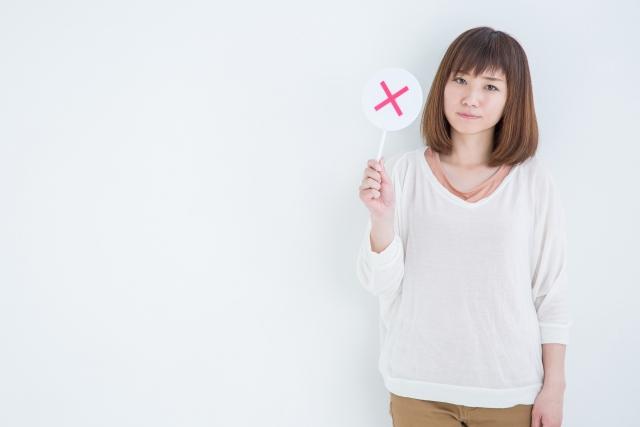 バツの札を持つ女性